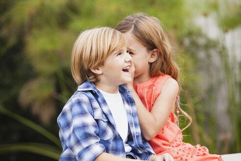 Girl whispering into boy's ear - WESTF020098