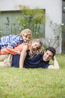 Happy father, daughter and son lying in grass - WESTF020115