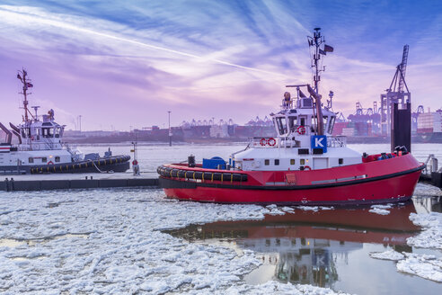 Germany, Hamburg, tugboats on icy Elbe river during sunrise - NK000205
