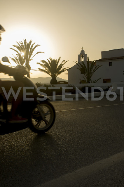 Spain, Balearic Islands, Ibiza, moped rider at sundown - TKF000402