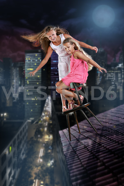 Two girls balancing on the spire over the night town - VT000346 - Val Thoermer/Westend61