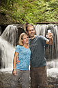 Germany, Rhineland-Palatinate, Moselsteig, Ehrbachklamm, couple taking selfie at waterfall - PAF001001