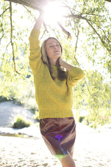 Young woman wearing knit pullover and mini skirt relaxing in nature - MAEF009185