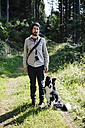Germany, Hesse, Man with Border Collie on forest path - DWF000196