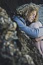 Teenage girl sitting on the beach - UUF002049