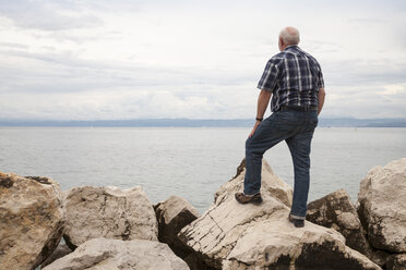 Slovenia, Piran, man standing on rocks at waterside looking at horizon - WIF001111
