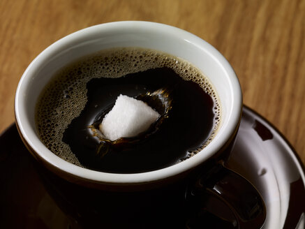 Sugar cube in cup of coffee - SRSF000520