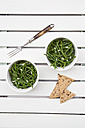 Two bowls of saltwort salad, fork and rye crackers on white wood - LVF001971