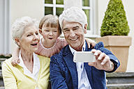 Germany, Hesse, Frankfurt, Senior couple taking selfie with granddaughter - RORF000052