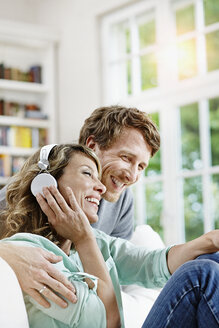 Germany, Hesse, Frankfurt, Adult couple at home listening to music - RORF000090