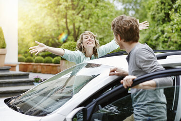 Happy woman with outstretched arms looking at man at car - RORF000109