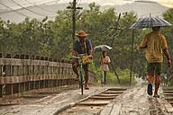 Myanmar, people on footbridge in monsoon rainfall - DSG000348