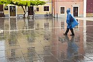 Slovenia, Koper, woman with rain cape crossing Carpaccio Square - WI001113