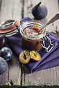 Opened preserving jar of plum fig jam on cloth and wood - SBDF001301