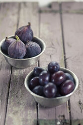 Two metal bowls of plums and figs on wood - SBDF001309