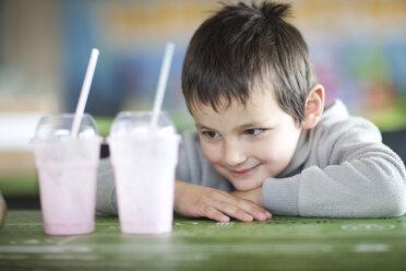 Smiling boy looking at empty milkshakecups in coffee shop - ZEF001254