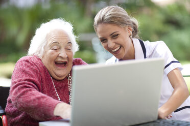 Happy nurse and senior woman using laptop together - ZEF001302
