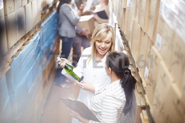 Two women with wine bottle in warehouse talking - ZEF001439