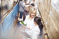 Two women with wine bottle in warehouse talking - ZEF001439