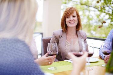 Friends drinking red wine on loggia - ZEF001772