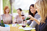 Woman pouring in glass of red wine with friends in background - ZEF001773