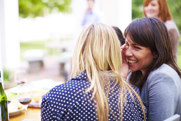Happy woman whispering to friend - ZEF001474