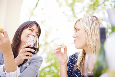 Two happy women with red wine and white bread - ZEF001476