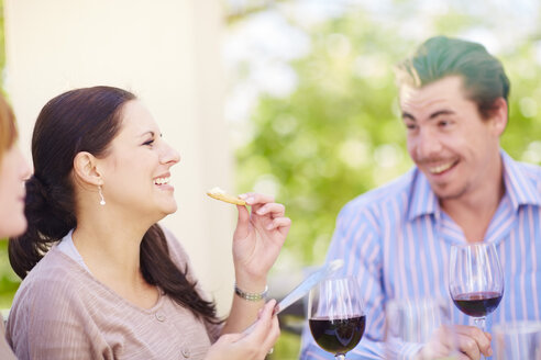 Happy friends with red wine glasses outdoors - ZEF001483