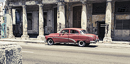 Cuba, red vintage car parking in front of old building with columns - NN000042