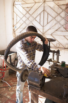 Cuba, Matanzas, Jaguey Grande, young man working at bicycle repair shop - NN000075