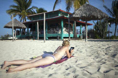 Cuba, Cayo Coco, female tourist lying on the beach reading ebook - NNF000078