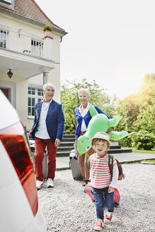Grandparents with granddaughter and luggage on driveway - RORF000113