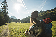 Austria, Tyrol, Tannheimer Tal, young female hiker with binocular and backpack watching landscape - UUF002108