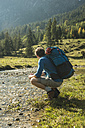 Austria, Tyrol, Tannheimer Tal, young hiker with backpack watching landscape - UUF002100