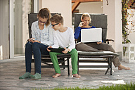 Mother and her two children relaxing with digital tablet, smartphone and laptop on the terrace - PAF001009