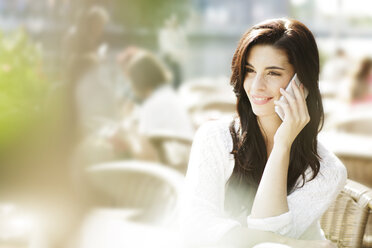 Smiling young woman telephoning with smartphone at a pavement cafe - GDF000469