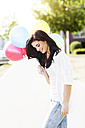 Smiling young woman with a bunch of balloons - GDF000482