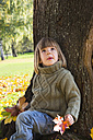 Little girl leaning at tree trunk looking up - LVF002003