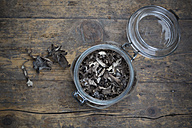 Preserving jar of dried black chanterelles, Craterellus cornucopioides, on dark wood - LVF001993