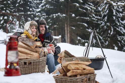 Smiling couple in snow with firewood - HHF004949