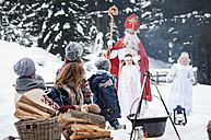 Family looking at angels and Santa Claus in snow - HHF004952