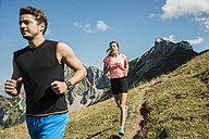 Austria, Tyrol, Tannheim Valley, young couple jogging in mountains - UUF002052