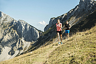 Austria, Tyrol, Tannheim Valley, young couple jogging in mountains - UUF002140
