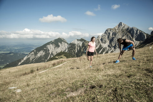 Austria, Tyrol, Tannheim Valley, young couple stretching in mountains - UUF002055