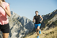 Austria, Tyrol, Tannheim Valley, young couple jogging in mountains - UUF002062