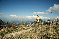 Austria, Tyrol, Tannheim Valley, young woman nordic walking in mountains - UUF002079
