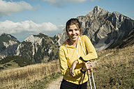 Austria, Tyrol, Tannheim Valley, smiling young woman holding nordic walking sticks in mountains - UUF002082