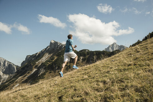 Austria, Tyrol, Tannheim Valley, young man jogging in mountains - UUF002090
