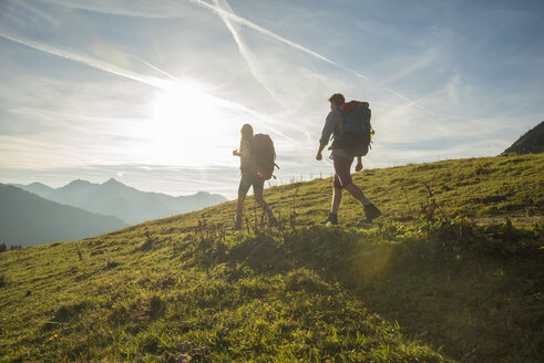 Austria, Tyrol, Tannheimer Tal, young couple hiking on alpine meadow - UUF002227