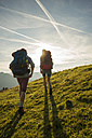 Austria, Tyrol, Tannheimer Tal, young couple hiking on alpine meadow - UUF002232